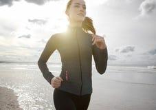 跑步户外由海滩的妇女 免版税库存图片