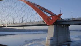 跑步横跨在冬天河上的工业现代桥梁的孤立都市运动员 股票录像