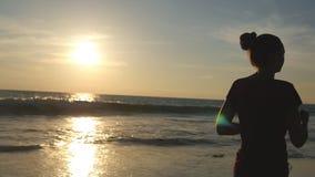 跑步沿海洋岸的女孩在日出期间 跑在海海滩的少妇剪影在日落 女性 股票录像