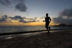 跑步沿海滩的赛跑者剪影 图库摄影