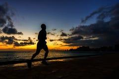 跑步沿海滩的赛跑者剪影 免版税图库摄影