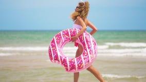 跑步用可膨胀的多福饼的年轻女人,与在海滩的可膨胀的圆环 影视素材
