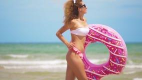 跑步用可膨胀的多福饼的年轻女人,与在海滩的可膨胀的圆环 股票视频