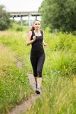 跑步的妇女在夏天午间 免版税库存图片