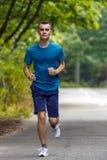 跑步通过森林的年轻男孩 免版税库存照片