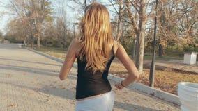 跑步通过美丽的秋天公园的亭亭玉立的女孩 影视素材