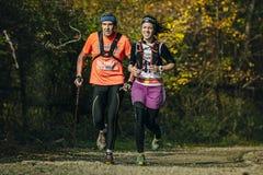 跑沿一个老男人和少妇在秋天森林里 免版税库存图片