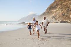 跑沿与孙的海滩的祖父母暑假 库存图片