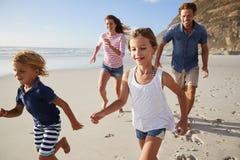跑沿与孩子的海滩的父母暑假 库存照片