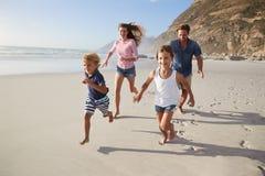跑沿与孩子的海滩的父母暑假 免版税库存图片