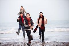 跑沿冬天海滩的家庭 库存照片