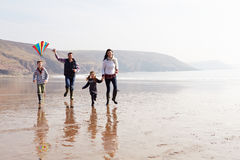 跑沿冬天海滩飞行风筝的家庭 免版税库存图片