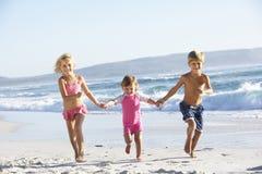 跑沿在游泳衣的海滩的小组孩子 免版税库存图片
