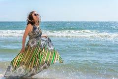 跑沿在礼服的黑海海滩的一名俏丽的妇女反对天空 免版税图库摄影