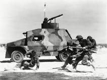 跑沿坦克的边的战士在沙漠 免版税库存照片
