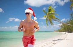 跑沿夏天海滩的愉快的人在圣诞节 免版税库存图片