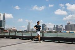 跑沿江边小游艇船坞海湾的运动员在新加坡 免版税库存图片