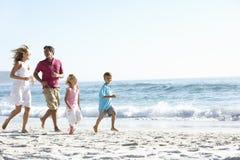 跑沿沙滩的年轻家庭在度假 免版税库存照片