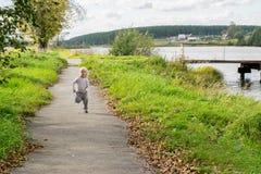 跑沿河岸的白肤金发的男孩 免版税库存图片