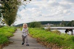 跑沿河岸的白肤金发的男孩 图库摄影