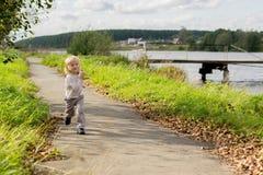 跑沿河岸的白肤金发的男孩 库存图片