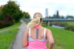 跑沿河的白肤金发的妇女 免版税库存照片
