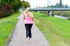 跑沿河的白肤金发的妇女 库存照片