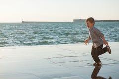 跑沿沿海的滑稽的逗人喜爱的小男孩在城市 免版税库存图片