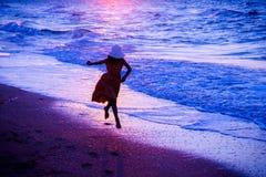 跑沿海浪的女孩 免版税库存图片