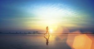 跑沿海滩的一个女孩的剪影 免版税库存照片