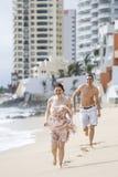 跑沿海滩的一对有吸引力的夫妇 免版税图库摄影