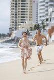 跑沿海滩的一对有吸引力的夫妇 库存照片