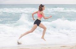 跑沿海滩的可爱的运动的妇女 库存照片