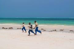 跑沿海滩的桑给巴尔男小学生 图库摄影