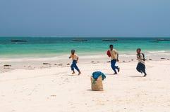 跑沿海滩的桑给巴尔男小学生 免版税库存照片