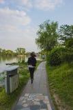 跑沿湖的女孩 库存照片