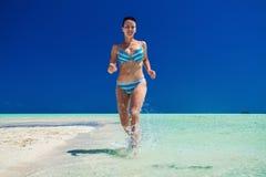 跑沿热带海滩的游泳衣的可爱的女孩 免版税库存照片