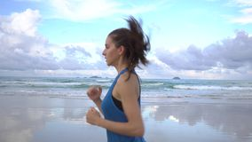 跑沿着岸线的健康活跃少妇在日出 女性跑步 股票录像