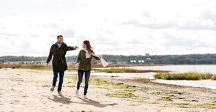 跑沿秋天海滩的夫妇 免版税库存图片