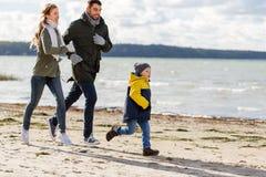 跑沿秋天海滩的愉快的家庭 免版税库存图片