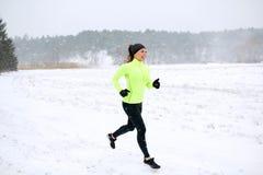 跑沿积雪的冬天路的愉快的妇女 图库摄影