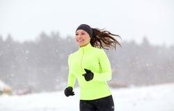 跑沿积雪的冬天路的愉快的妇女 免版税库存图片