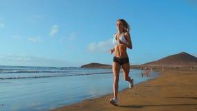 跑沿美丽的沙滩,健康生活方式的美丽的嬉戏妇女,享受活跃暑假近 股票视频