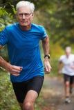 跑沿道路的两位成熟公慢跑者 免版税库存照片