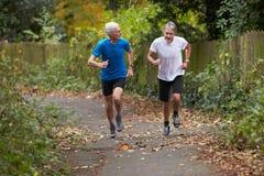 跑沿道路的两位成熟公慢跑者 图库摄影