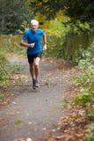 跑沿道路的成熟公慢跑者 免版税库存照片