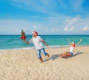 跑海上的年轻夫妇在有雪撬和ch的圣诞老人帽子靠岸 免版税库存图片