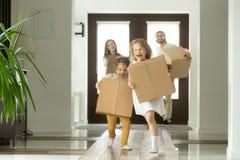 跑激动的孩子拿着箱子,移动在新房里的家庭 免版税库存图片
