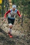 跑用棍子的微笑的运动员走在压缩袜子 免版税库存照片