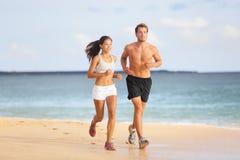 跑的人们-跑步在海滩的年轻夫妇 图库摄影